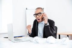 Ritratto di un uomo d'affari arrabbiato con il telefono cellulare Fotografia Stock