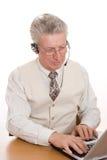 Ritratto di un uomo di affari che si siede dal suo computer portatile Immagini Stock