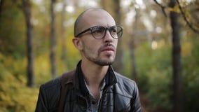 Ritratto di un uomo facente smorfie in vetri nel parco di autunno archivi video