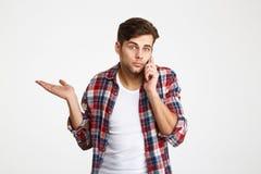 Ritratto di un uomo imbarazzato confuso che parla sul telefono cellulare Fotografie Stock Libere da Diritti