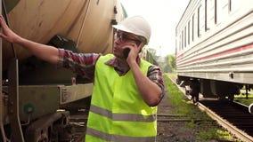 Ritratto di un uomo nel lavoratore di vetro in un casco ed in un'uniforme, camminante sulla stazione ferroviaria parlante sul tel video d archivio