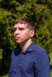 Ritratto di un uomo nell'esterno diritto della camicia blu in parco immagini stock libere da diritti