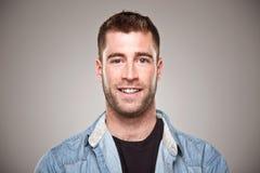 Ritratto di un uomo normale che sorride sopra il fondo grigio Fotografia Stock