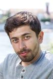 Ritratto di un uomo sorridente con la barba in una camicia grigia fuori Immagini Stock Libere da Diritti