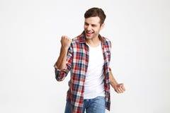 Ritratto di un uomo sorridente emozionante che celebra successo Fotografie Stock Libere da Diritti