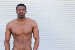 Ritratto di un uomo tonificato e strappato magro di forma fisica del muscolo nell'ambito di illuminazione morbida con lo spazio d immagini stock