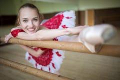 Ritratto di una ballerina che fa l'allungamento delle gambe vicino al Immagine Stock Libera da Diritti