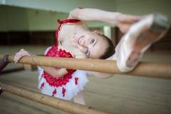 Ritratto di una ballerina che fa l'allungamento delle gambe vicino al Fotografie Stock Libere da Diritti