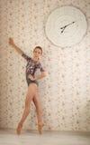 Ritratto di una ballerina professionista sulla punta dei piedi vicino alla finestra alla luce del sole nell'interno domestico Con Fotografia Stock Libera da Diritti