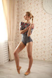 Ritratto di una ballerina professionista vicino alla finestra alla luce del sole nell'interno domestico Immagini Stock