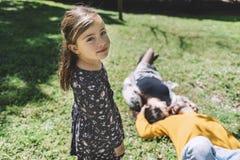 Ritratto di una bambina adorabile che esamina macchina fotografica mentre i suoi genitori che mettono su terra in un giorno soleg fotografia stock