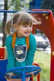 Ritratto di una bambina che conduce un'automobile su un campo da giuoco Fotografie Stock Libere da Diritti