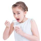 Ritratto di una bambina che mangia yogurt. Fotografia Stock