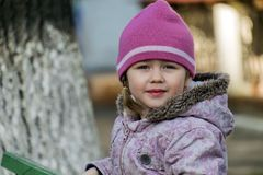 Ritratto di una bambina con una breve treccia che guarda fuori da sotto il cappello magenta della molla fotografie stock