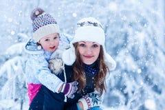 Ritratto di una bambina e di sua madre in cappello di inverno in neve f Immagini Stock Libere da Diritti
