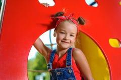 Ritratto di una bambina graziosa in denim complessivo con la camicia e il handkerchie rossi fotografia stock