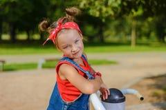 Ritratto di una bambina graziosa in denim complessivo con la camicia e il handkerchie rossi immagine stock libera da diritti