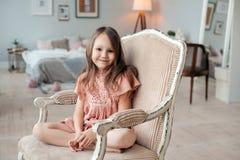 Ritratto di una bambina sveglia che si siede nella sedia nella sua stanza Fotografia Stock Libera da Diritti