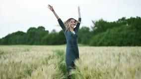 Ritratto di una bionda caucasica attraente felice con capelli bagnati che filano nella pioggia sulla natura Campo di grano all'ap stock footage