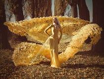 Ritratto di una bionda che porta un abito fiorito e dorato fotografia stock libera da diritti