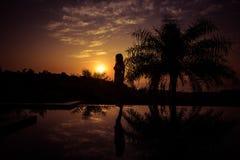Ritratto di una condizione della giovane donna contro un tramonto splendido fotografia stock