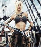 Ritratto di una condizione femminile del pirata biondo sulla piattaforma della sua nave con la spada a disposizione illustrazione di stock