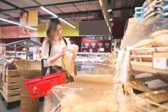 Ritratto di una condizione graziosa della ragazza nel dipartimento del pane di un supermercato con un pacchetto di carta fotografia stock