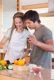 Ritratto di una coppia che cucina mentre bevendo vino Immagini Stock