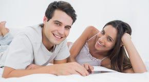 Ritratto di una coppia facendo uso di una compressa che si trova a letto Immagini Stock Libere da Diritti