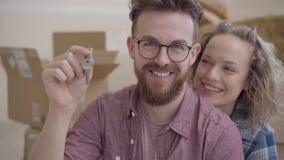 Ritratto di una coppia nell'amore, hanno comprato appena una casa e muoversi L'uomo barbuto in vetri mostra la chiave, donna sveg video d archivio