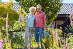 Ritratto di una coppia senior attiva che tiene gli strumenti di giardinaggio nel giardino immagini stock