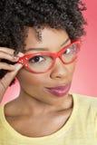 Ritratto di una donna afroamericana che indossa i retro vetri sopra fondo colorato Fotografia Stock Libera da Diritti