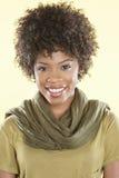 Ritratto di una donna afroamericana che sorride con una stola rotonda il suo collo sopra fondo colorato fotografie stock