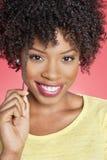 Ritratto di una donna afroamericana che sorride sopra il fondo colorato immagine stock libera da diritti