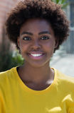 Ritratto di una donna afroamericana tipica in una camicia gialla Fotografia Stock
