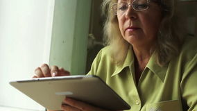 Ritratto di una donna all'età con il PC della compressa