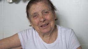 Ritratto di una donna anziana con le grinze sul suo fronte che esamina macchina fotografica e sorridere video d archivio