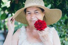 Ritratto di una donna anziana con una rosa rossa tonalità selettivo Fotografia Stock