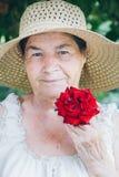Ritratto di una donna anziana con una rosa rossa tonalità selettivo Fotografia Stock Libera da Diritti