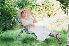 Ritratto di una donna anziana in un cappello che si trova sul lettino Immagine Stock