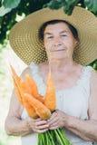 Ritratto di una donna anziana in un cappello che tiene una carota Fotografie Stock Libere da Diritti