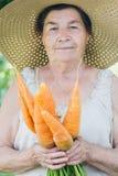 Ritratto di una donna anziana in un cappello che tiene una carota Fotografia Stock Libera da Diritti