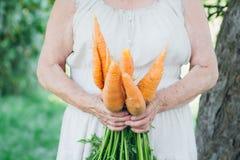 Ritratto di una donna anziana in un cappello che tiene una carota Immagine Stock Libera da Diritti
