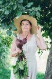 Ritratto di una donna anziana in un cappello tenendo le barbabietole Immagini Stock