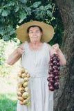 Ritratto di una donna anziana in un cappello tenendo le cipolle Fotografia Stock Libera da Diritti