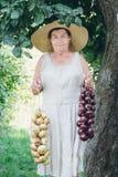 Ritratto di una donna anziana in un cappello tenendo le cipolle Immagine Stock Libera da Diritti