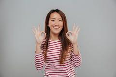 Ritratto di una donna asiatica felice che mostra gesto giusto Immagine Stock