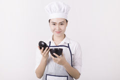 Ritratto di una donna asiatica in uniforme del cuoco unico che tiene una ciotola di riso Immagini Stock