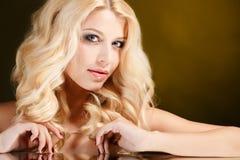 Ritratto di una donna bionda attraente con capelli ricci lunghi, isolato sul colpo nero dello studio Fotografie Stock