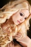 Ritratto di una donna bionda attraente con capelli ricci lunghi, isolato sul colpo nero dello studio Fotografie Stock Libere da Diritti
